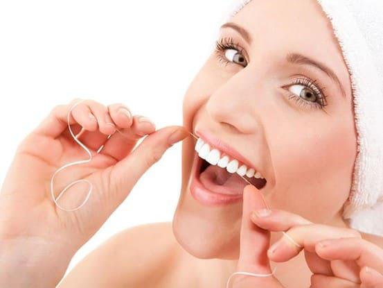 Sử dụng chỉ nha khoa để loại bỏ thức ăn thừa giắt dính kẽ răng