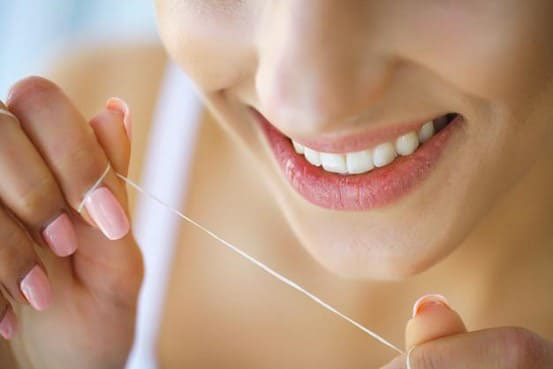 Dùng chỉ tơ nha khoa để loại bỏ thức ăn dính trong kẽ răng